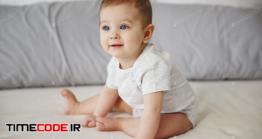 دانلود عکس استوک : نوزاد در تخت خواب Adorable Baby Girl Sitting On Bed