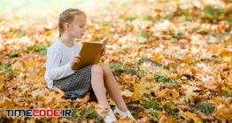 دانلود عکس استوک : دختر نوجوان در حال مطالعه کتاب در پاییز Adorable Little Girl At Beautiful Autumn Day Outdoors