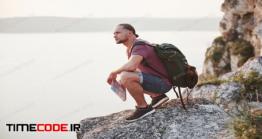 دانلود عکس استوک : کوه نورد در نشسته در بالای کوه Attractive Man Enjoying The View Of The Mountains