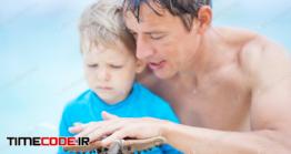 دانلود عکس استوک : پدر و پسر در استخر Father And Son Watching Starfish Sticking To Man's Hand
