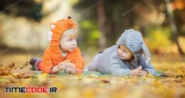 دانلود عکس استوک : دو نوزاد با لباس حیوانات در پارک Little Children In Animal Costumes Playing In Autumn Forest