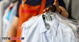 دانلود عکس تحویل لباس در خشکشویی به مشتری  Clothes Dry Cleaning Service Worker Returning Shirts To Customer
