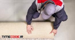 دانلود کارگر در حال پهن کردن فرش در خانه Male Worker Unrolling Carpet On Floor At Home