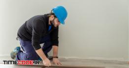 دانلود عکس کارگر ساختمانی در حال اجرا لمینت ساختمان Man Carpenter Assembling Laminate Flooring